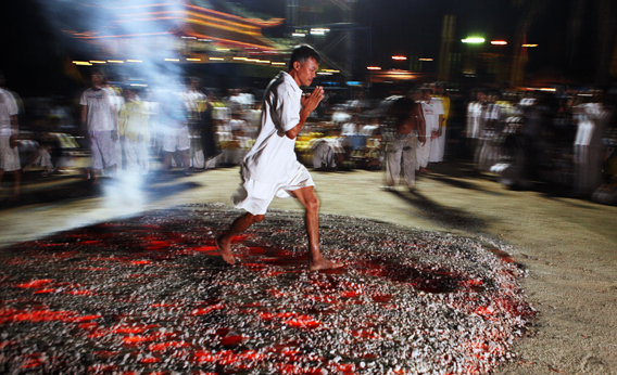 A devotee of Ban Tha Rue runs across hot coals during a night procession at a Vegetarian Festival on October 16, 2007, in Phuket, Thailand.