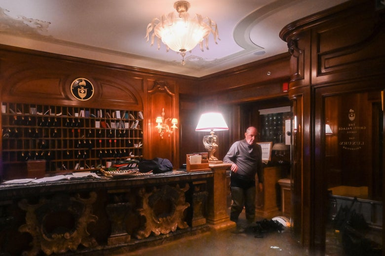 An employee stands by the flooded front desk of the Gritti Palace hotel.