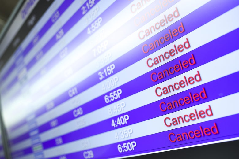 A display board shows canceled flights at the airport.