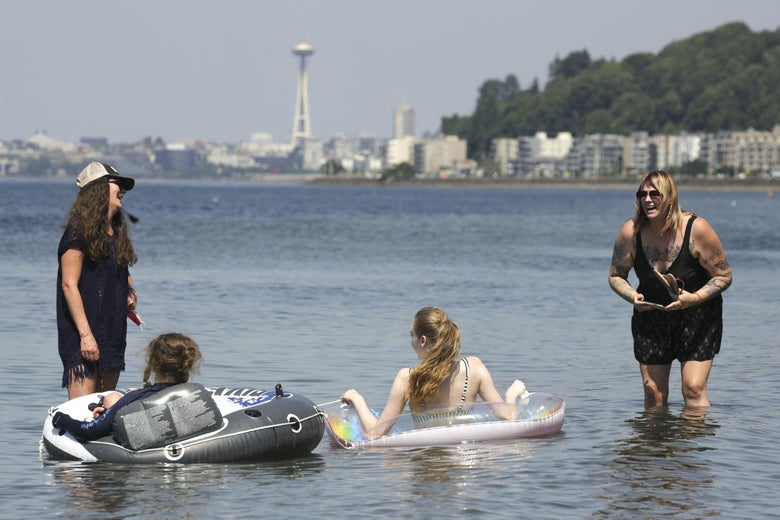 Two women and their kids, sitting in the tubes, cool off at the beach