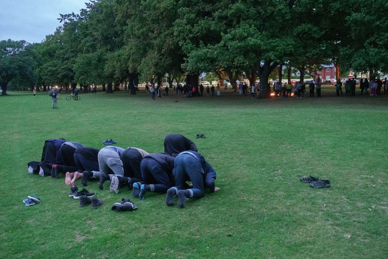 Eight men kneel to pray in a park.