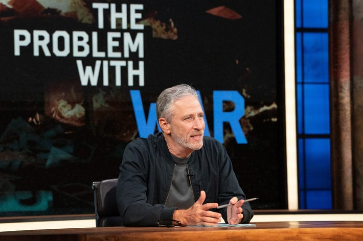 """Jon Stewart sits at a desk and gesticulates in front of a display reading, """"The Problem With War."""""""
