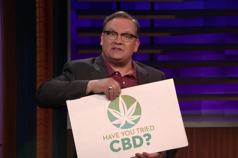 """Andy Richter holds a cue card reading """"Have you tried CBD?"""""""