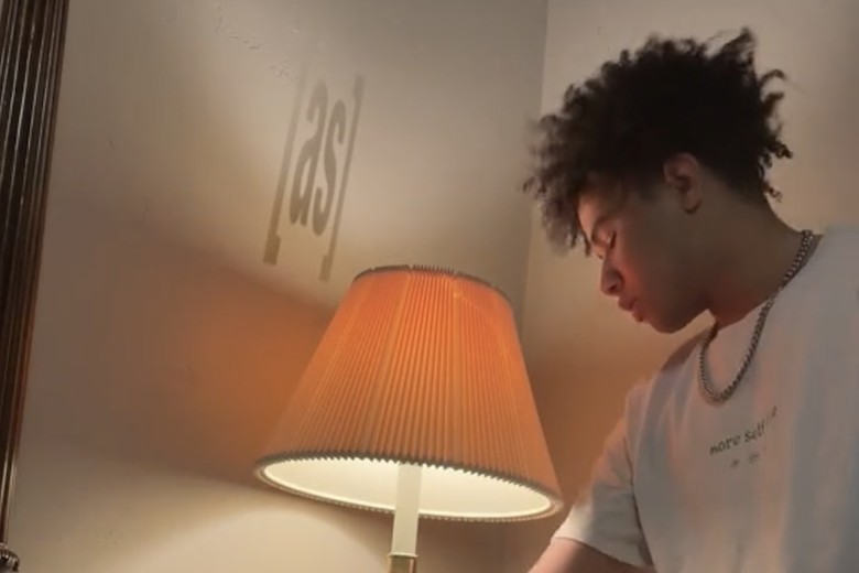 """A boy with curly black hair stands next a lamp that is turned on. Projected onto the wall is a faint image of the letters """"a"""" """"s"""" bracketed."""