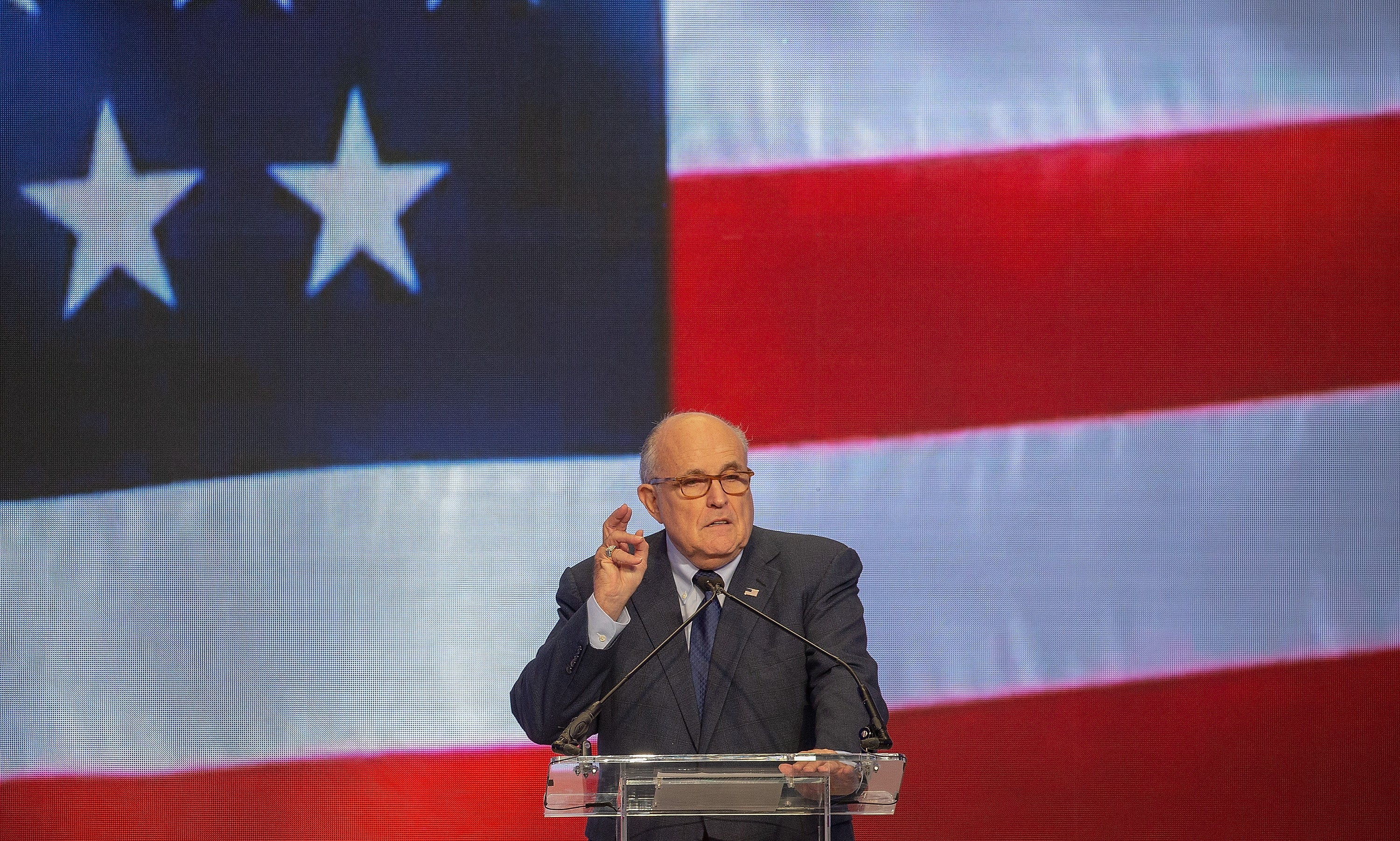Rudy Giuliani speaks at a conference in front of an electronic American flag backdrop.