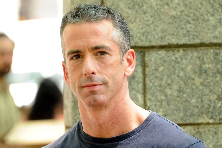 Dan Savage, outside against a cement wall.