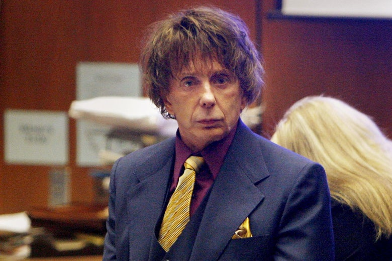 The producer stands up in a fancy suit and a long brown mop top that clearly doesn't match his age.