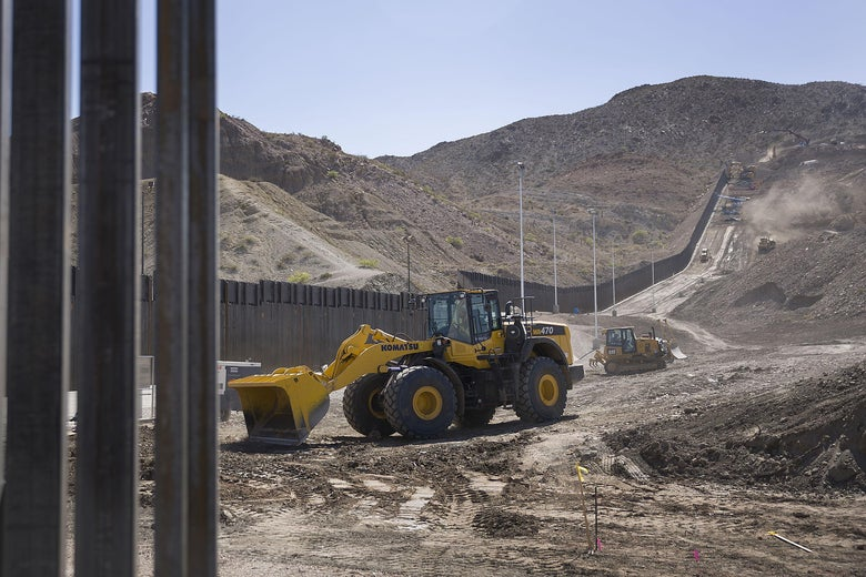 Construction crews work on a border wall.