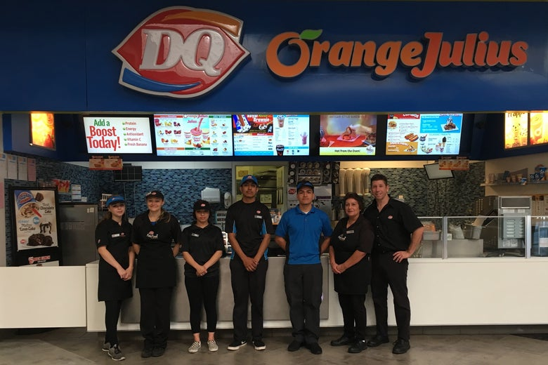 The staff of the Northridge Mall Dairy Queen, including franchise owner Rocco Frattaroli. They are posing in front of the location and the sign, as well as an Orange Julius sign.