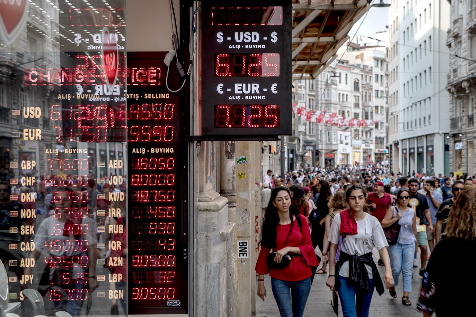 People walk past a currency exchange office on Aug. 29 in Istanbul.