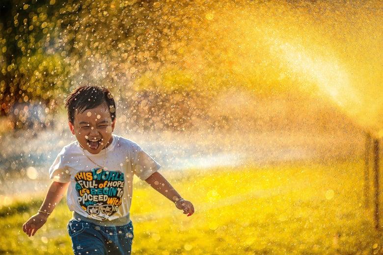 A young boy runs through a sprinkler.