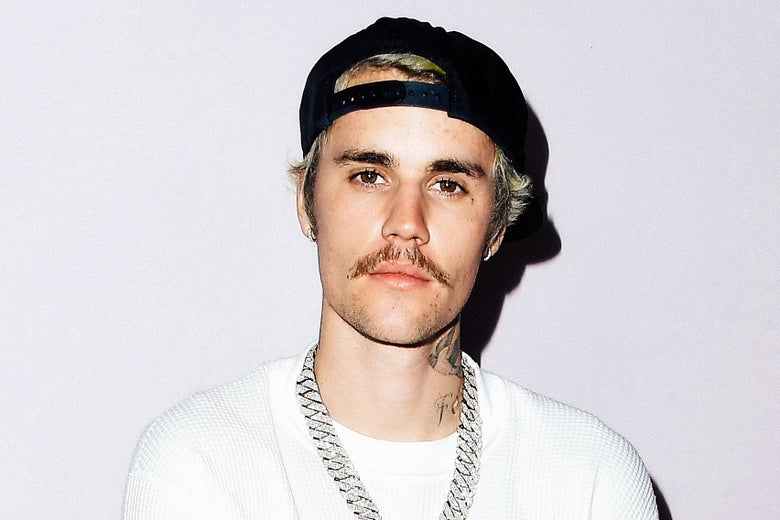Justin Bieber in a white shirt, black hat, and silver chain, sporting a mustache.