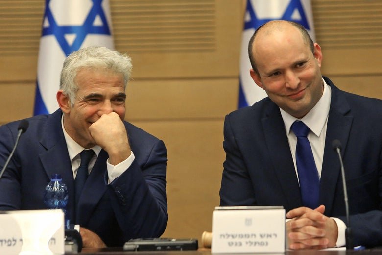 Israel's incoming Prime Minister Naftali Bennett (right) and Alternate Prime Minister and Foreign Minister Yair Lapid look on during an address at the Knesset in Jerusalem on June 13, 2021.