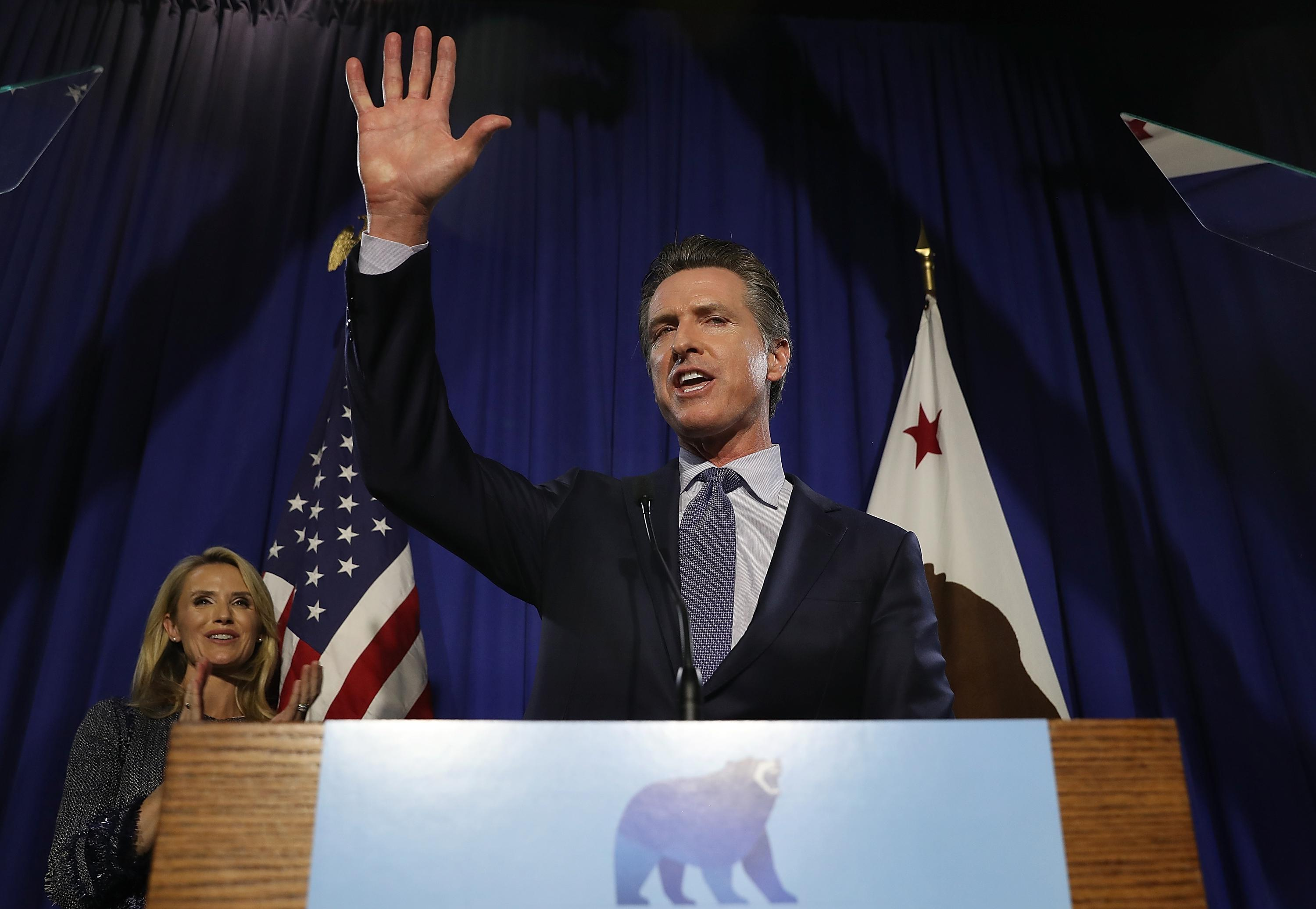 Gavin Newsom waves at the crowd.