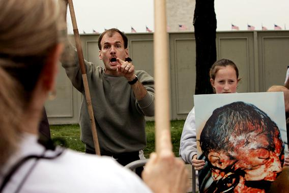 Pro Life Protester yelling alongside a graphic image of an aborted fetus.