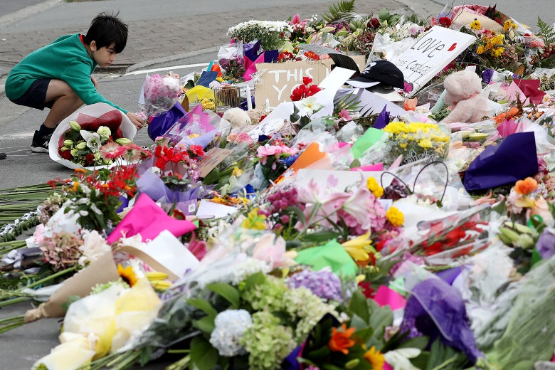 A little boy places flowers at a memorial to the Christchurch shooting victims.