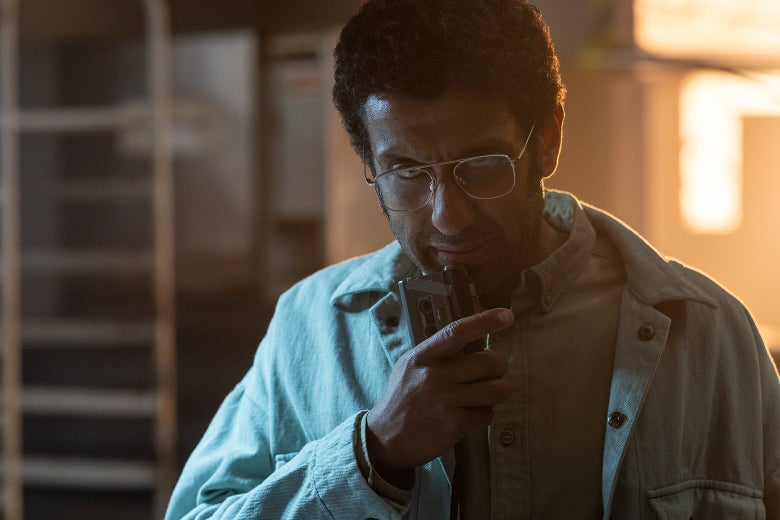 Actor Adeel Akhtar as Dr. Singh in a still from Sweet Tooth, wearing a denim shirt and speaking into a microcassete recorder.