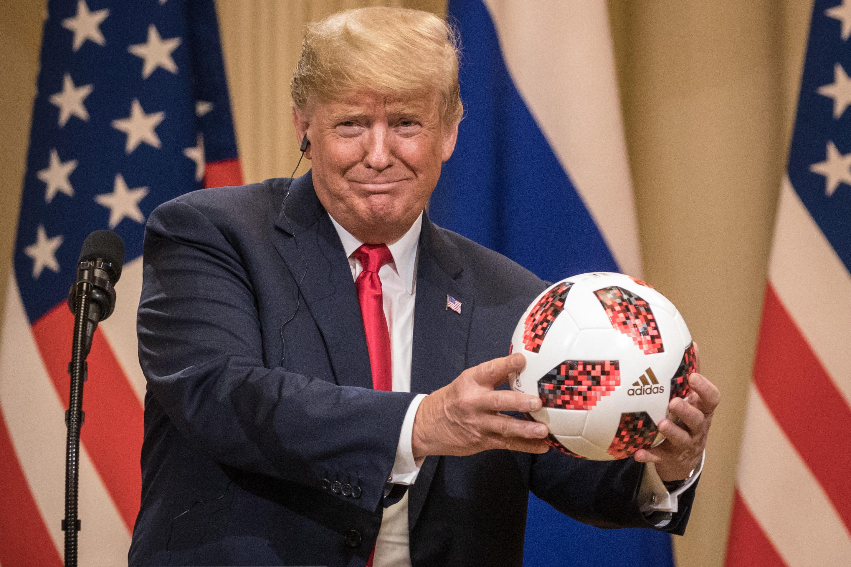 President Donald Trump holds a World Cup football given to him by Russian President Vladimir Putin during a joint press conference after their summit on July 16, 2018 in Helsinki, Finland.