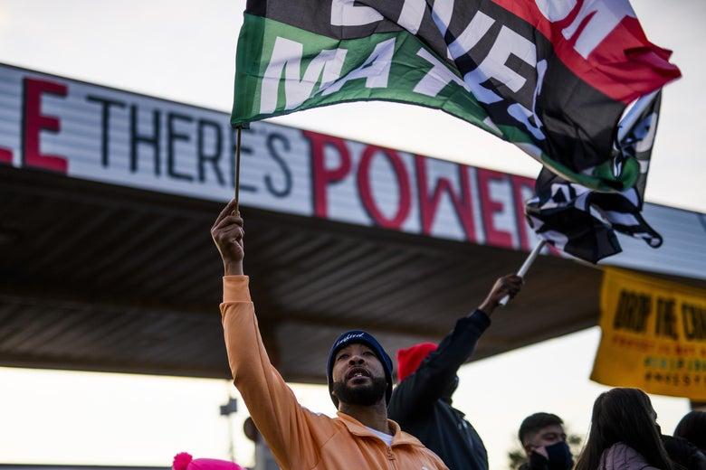 Man waving Black Lives Matter flag.