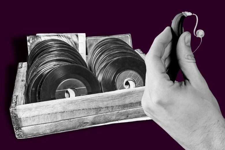 Someone holding a digital hearing aid in front of a stack of records.