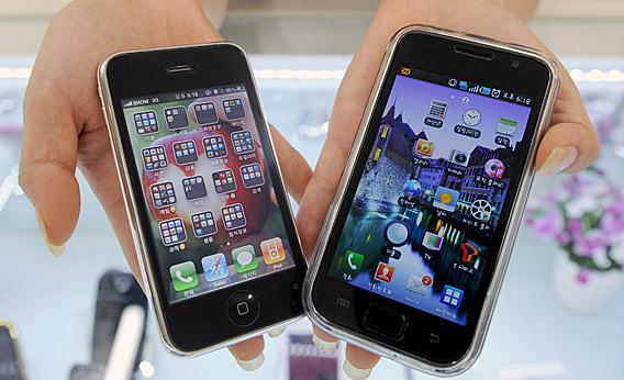 South Korea shop manager shows Samsung Electronics' Galaxy S mobile phone (R) and Apple's iPhone 3G at a shop in Seoul