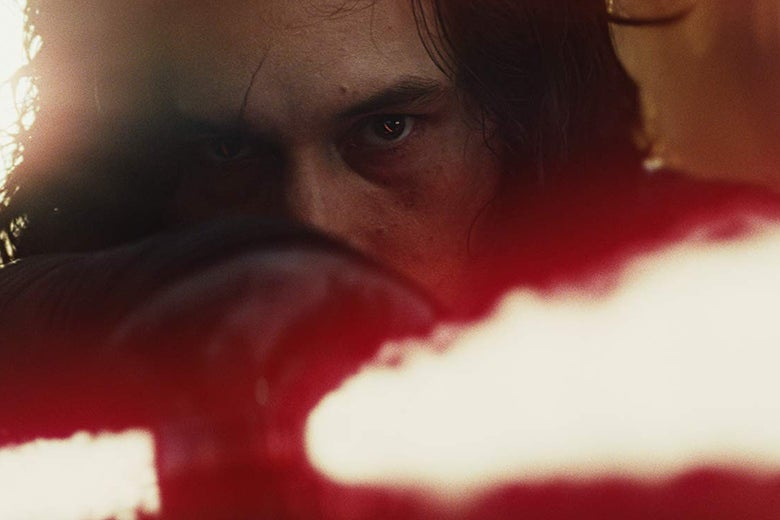 A close up of Adam Driver as Kylo Ren, peering over the red light of a lightsaber.