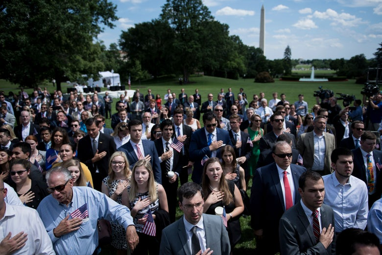 A group of one hundred or so individuals in professional dress, many of them young, on the lawn of the White House with the Washington Monument behind them.