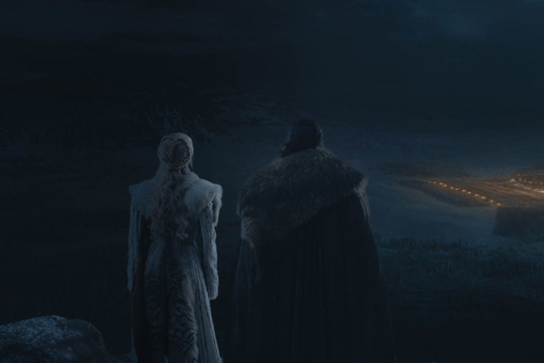 Daenerys and Jon Snow looking across a dark battlefield.