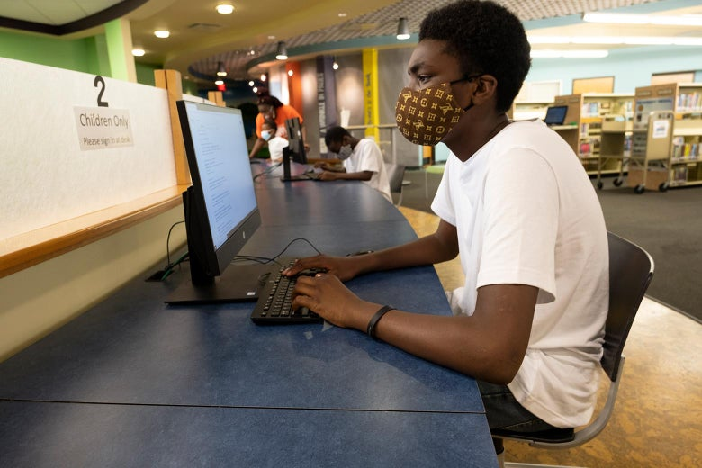 Teenage boy wearing a face mask working at a desktop computer in a public library. In the background, one of his brothers works at a different computer, and his mother stands beside the third brother, all three wearing masks.