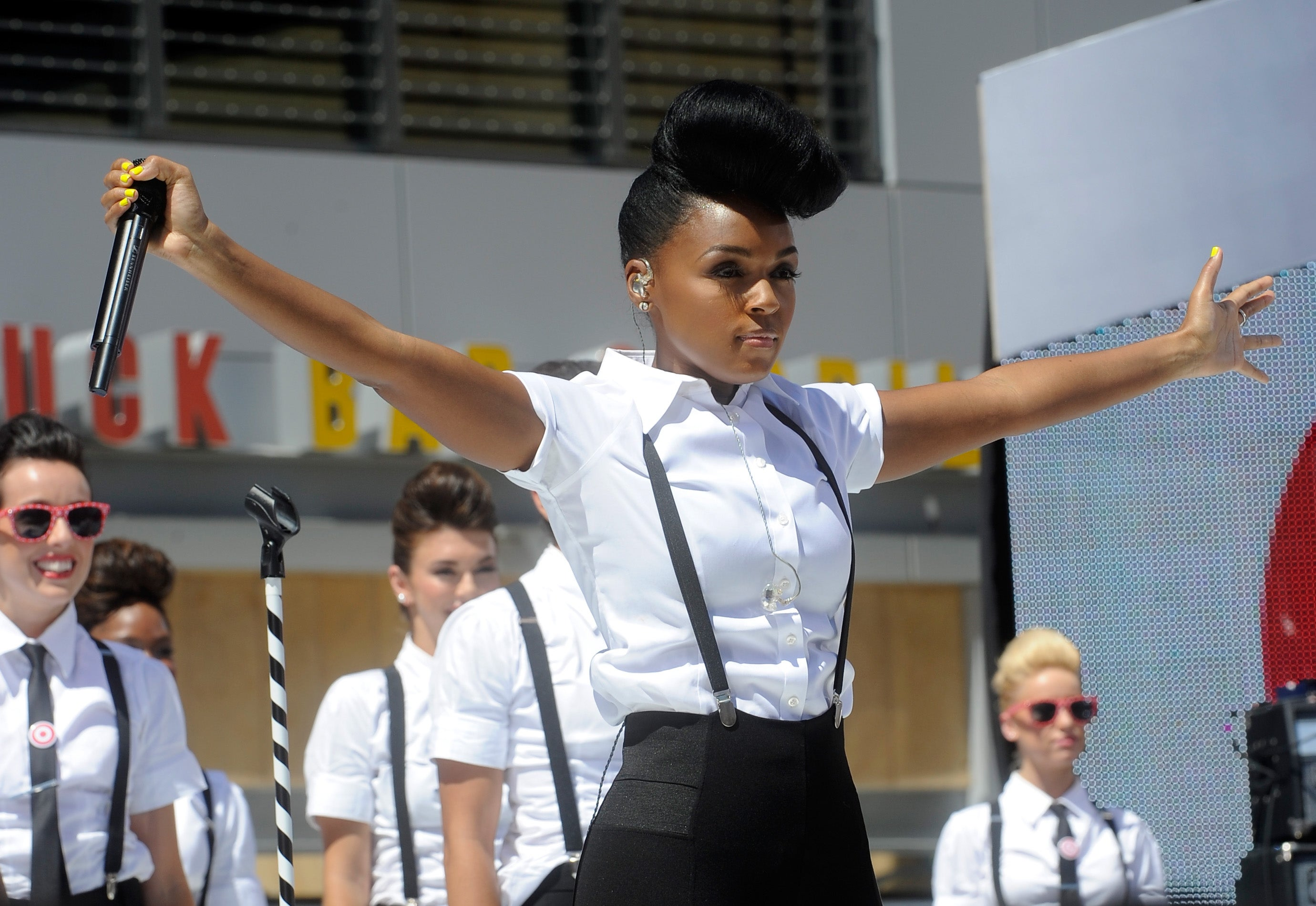 Recording Artist Janelle Monae performs onstage at 106 & Park Live presented by Target during the 2013 BET Exeperience at L.A. LIVE on June 28, 2013 in Los Angeles, California. She stands, arms outspread, her black suspenders standing out against her white, short-sleeved shirt.