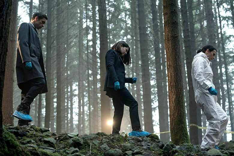 Three people walk through the woods with covers over their shoes.