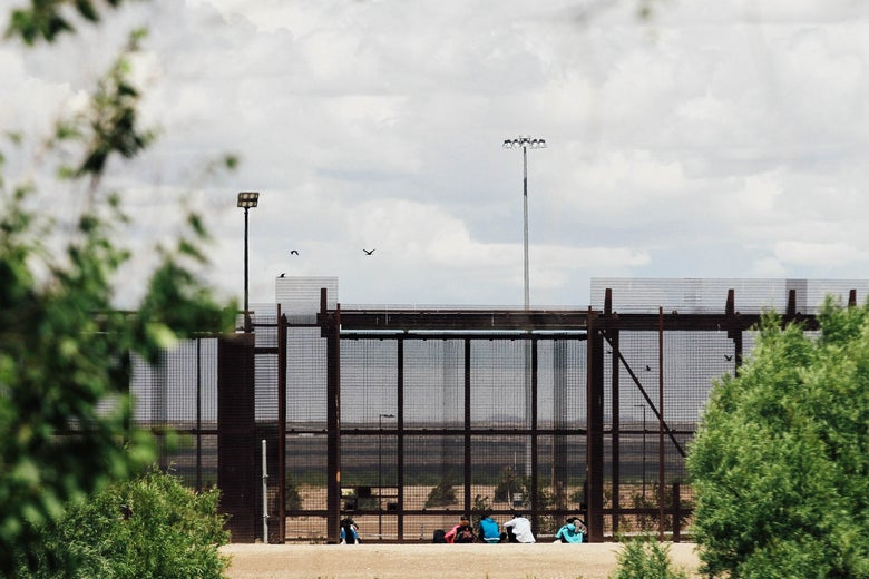 A group of migrants wait to be stopped by the Border Patrol at the border wall in El Paso, Texas as seen from Ciudad Juarez, Mexico on Wednesday.