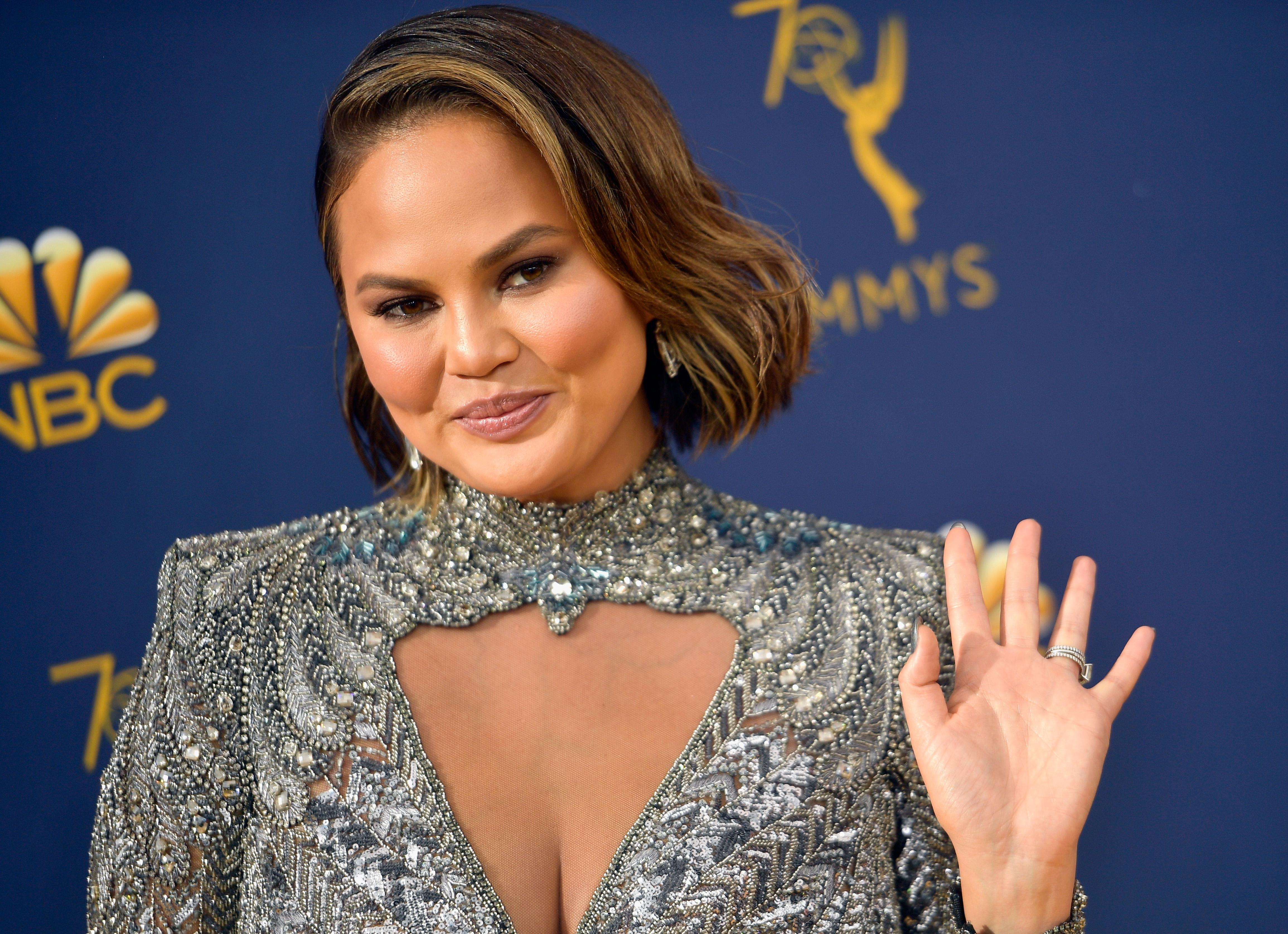 Chrissy Teigen waves at the camera, wearing a silver high-neck gown.
