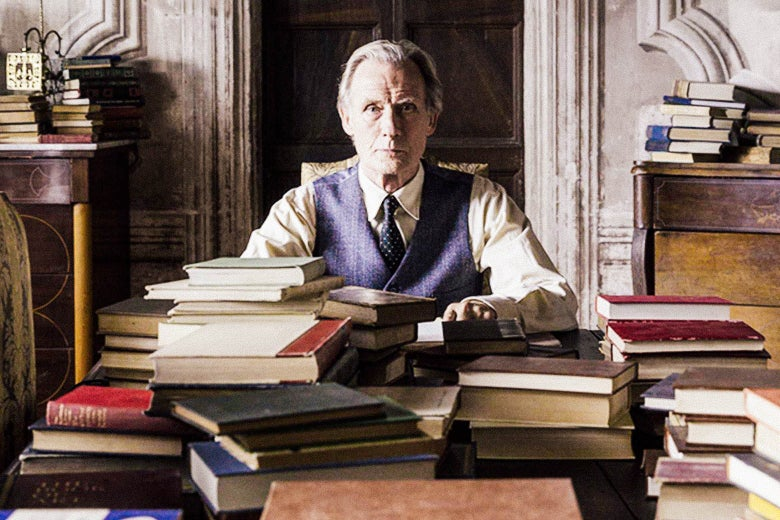 In a still from The Bookshop, Mr. Brundish (Bill Nighy) sits at a desk covered in and surrounded by books.