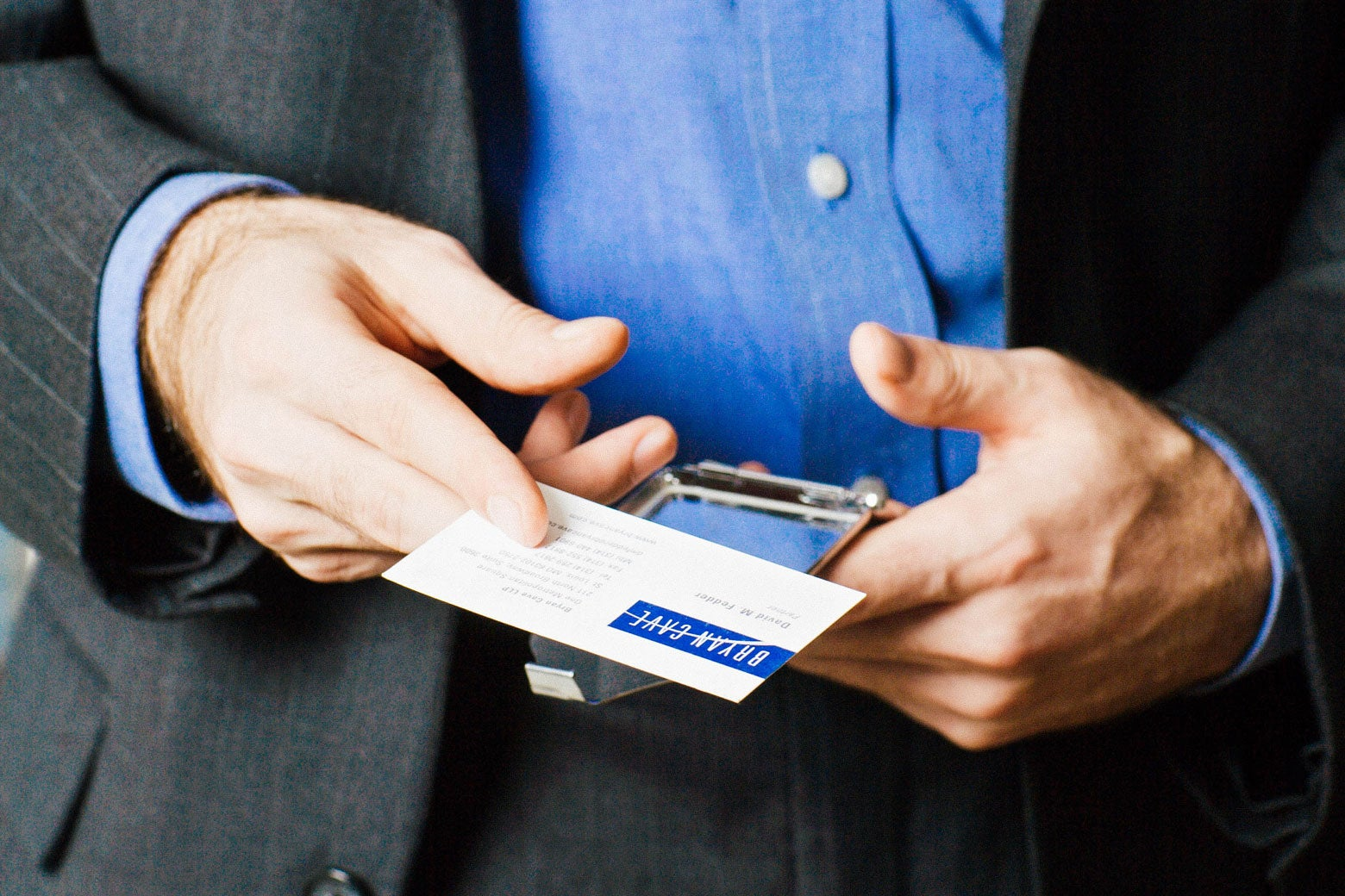 Stock image of a man holding out a business card.