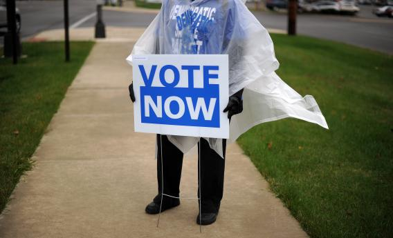 An Ohio Democratic Party volunteer displays a placard to encourage public for early voting in front of an early voting center.