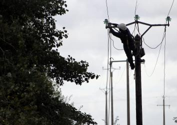 An electric company worker repairs damaged power lines damaged northwestern France.