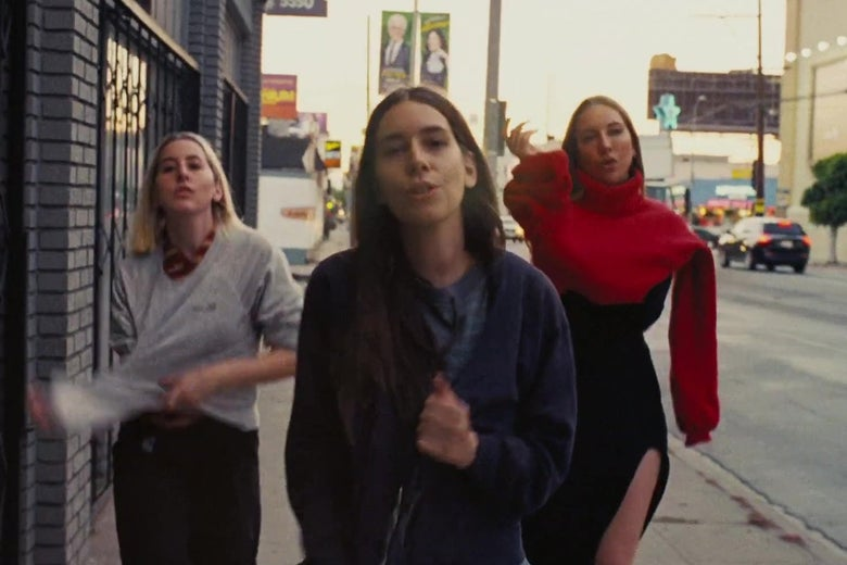 The band Haim walking toward camera down Melrose Avenue, with an Astro Burger and the Paramount lot in the background.