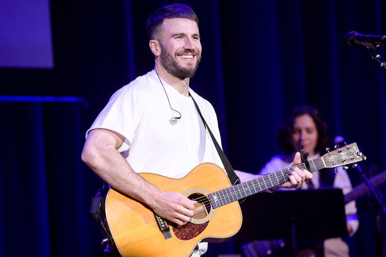 Sam Hunt in a white T-shirt holding an acoustic guitar.