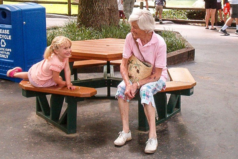 More recent photo of Alice on a picnic bench with a child.