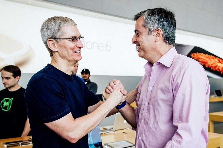 Tim Cook shakes Eddy Cue's hand in a sort of arm wrestling pose at an Apple Store for the iPhone 6 launch.