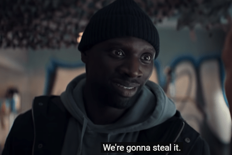 """A man in a knitted beanie stands in front of a wall with graffiti; subtitles say, """"We're gonna steal it."""""""