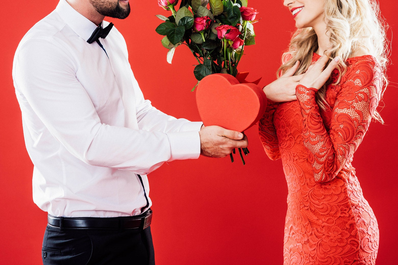 Man giving a woman chocolates and flowers for Valentine's Day.