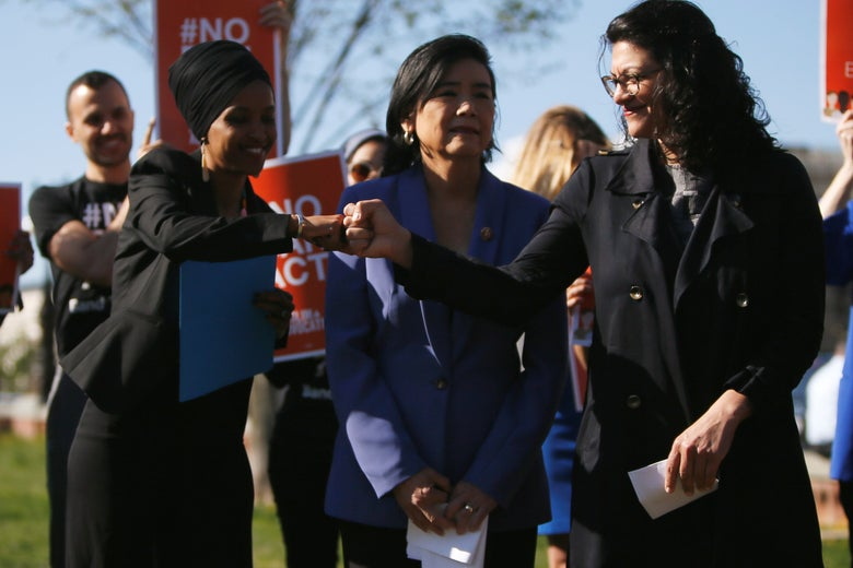Rep. Ilhan Omar (L) shares a fist bump with Rep. Rashida Tlaib (R) in Washington, D.C., April 10, 2019.