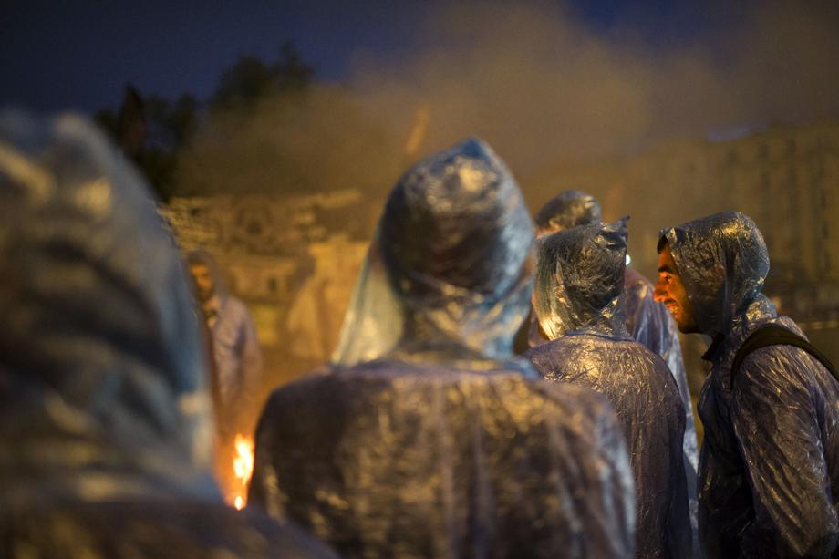 Protesters warm themselves by a fire as morning breaks at the Gezi park in Taksim Squareon June 5, 2013 in Istanbul, Turkey.