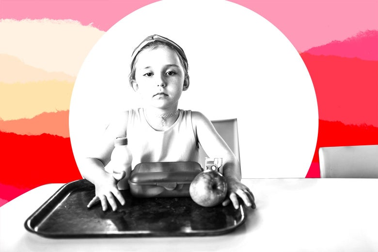 A young girl sits in front of a school lunch tray with an apple and milk.