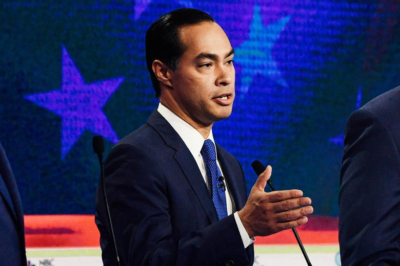 Julián Castro gestures from behind his podium on the debate stage.