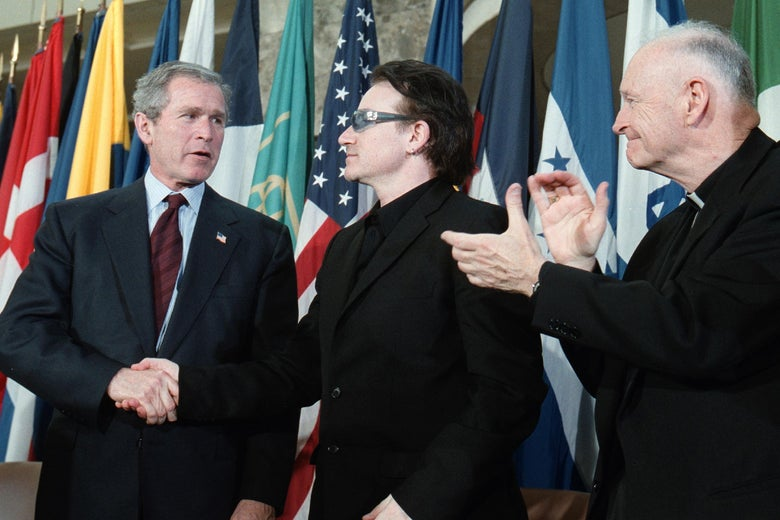 George W. Bush shaking hands with Bono, as Theodore McCarrick looks on, applauding.