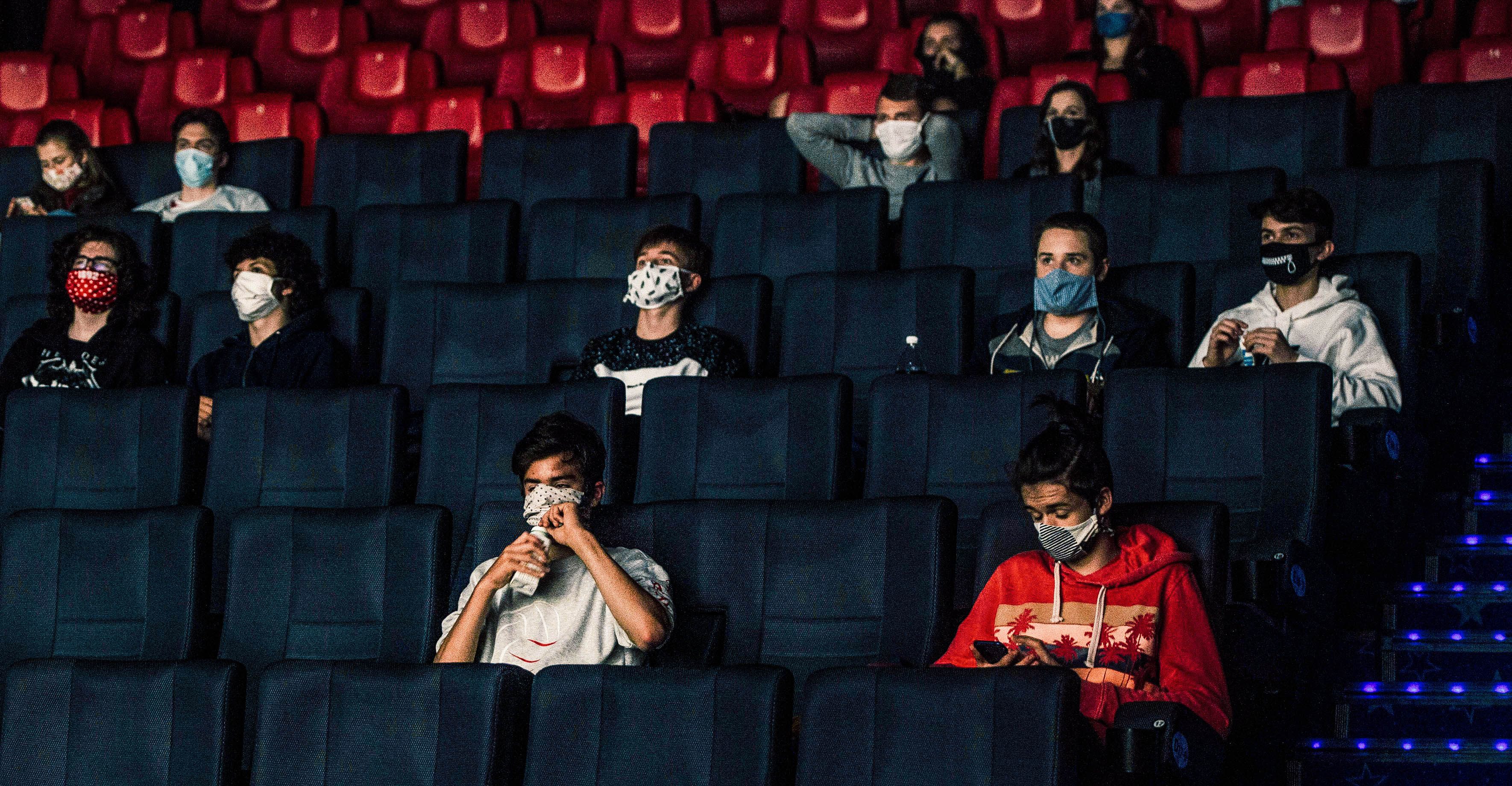 People wearing masks inside of a movie theater.