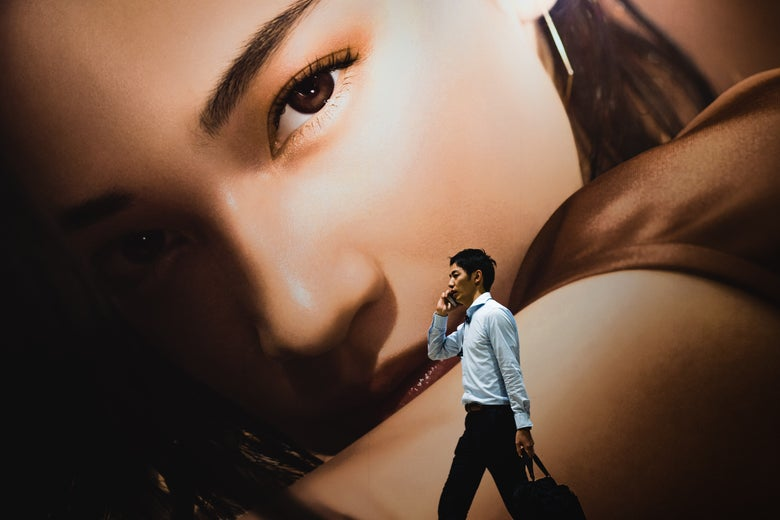 A man on a cellphone walks in front of an enormous image of a woman's face and arm.